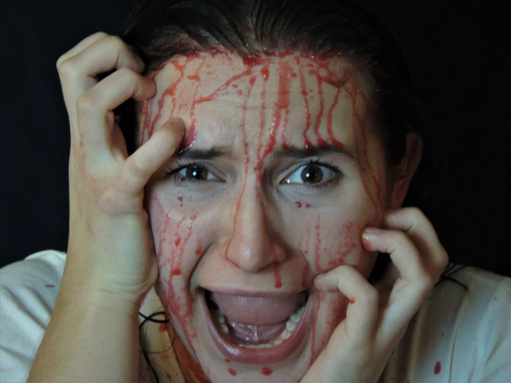 A woman clutching her face and screaming, with blood covering her face.