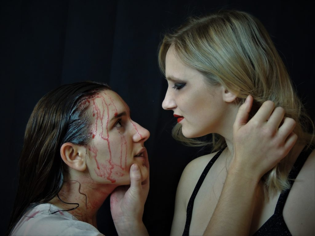 two women holding each other's faces tenderly, one is bloodied and the other wears makeup