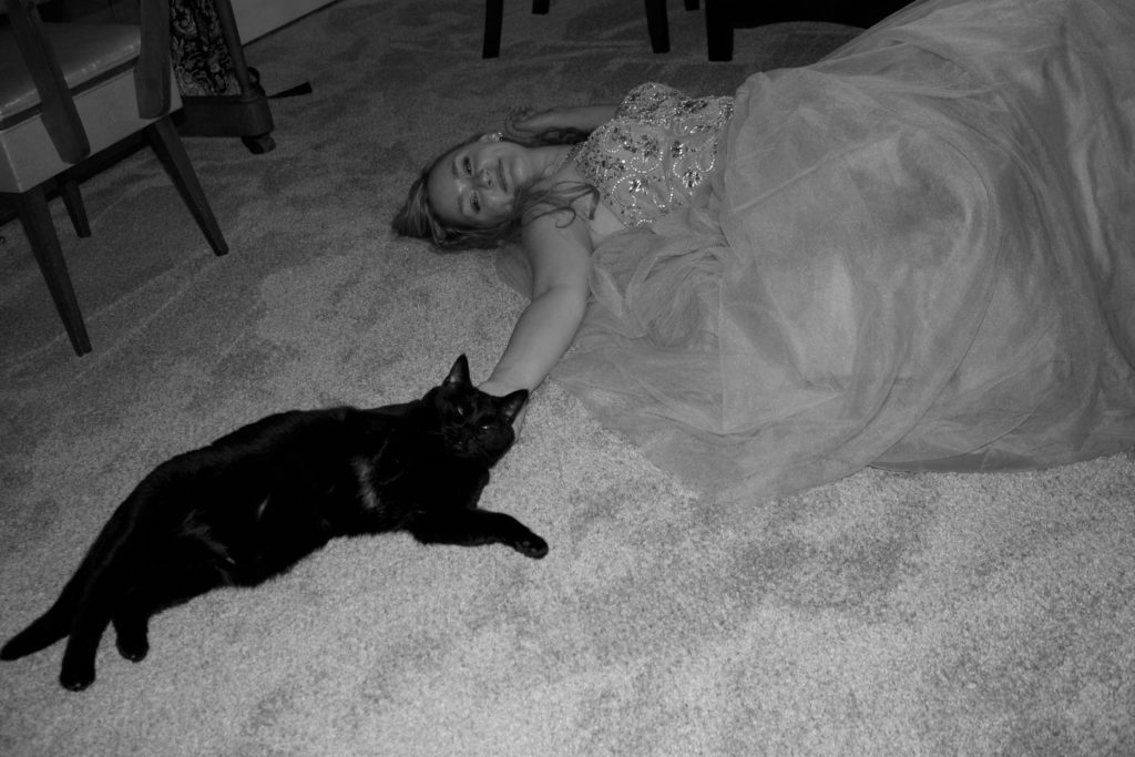the author's cat Lucy and her laying on her living room floor after senior prom, her cinderella ballgown spread out around her, circa 2016.
