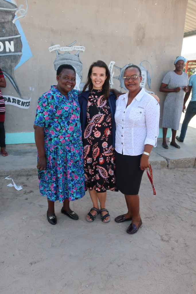 An American Peace Corps Volunteer standing with two Namibian teachers